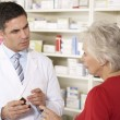 Foto Stock: Americpharmacist with senior womin pharmacy