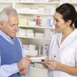 Foto de Stock  : Americpharmacist serving senior min pharmacy