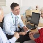 British GP talking to senior couple in surgery — Stock Photo