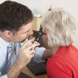 British doctor examining senior woman's ear — Stock Photo