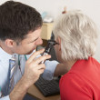 British doctor examining senior woman's ear - Stock Photo