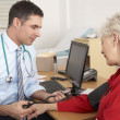 British doctor taking senior woman's blood pressure — Stock Photo