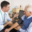 Stockfoto: British doctor taking senior man's blood pressure