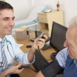 British doctor taking senior man's blood pressure — Stock Photo