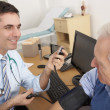 British doctor taking senior man's blood pressure — Stock Photo #11887890
