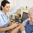 British nurse giving injection to senior man - Stockfoto