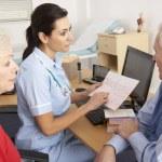 British nurse talking to senior couple — Stock Photo