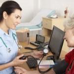 British nurse taking senior woman's blood pressure — Stock Photo #11887918