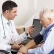 Stock Photo: Americdoctor taking senior man's blood pressure