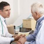 American doctor talking to senior man in surgery — Stock Photo #11887975