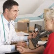 American doctor taking senior woman&amp;#039;s blood pressure - Stock Photo