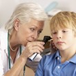 British GP examining young boy's ear — Stock Photo #11888020
