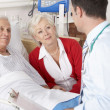 Stock Photo: Doctor talking to senior couple on UK Hospital ward
