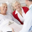 Doctor talking to senior couple on UK Hospital ward — Stock Photo