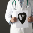 Americdoctor holding ink drawing of heart — Stock Photo #11888269