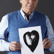 Senior man holding ink drawing of heart — Foto de Stock