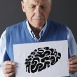 Senior man holding ink drawing of brain - Stock Photo