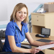 Portrait UK doctor sitting at desk — Stock Photo