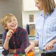 Mother and son preparing food in domestic kitchen — Foto de Stock