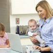 Stock Photo: Mother with children using laptop in kitchen