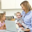 Mother with children using laptop in kitchen — Stock Photo #11888766