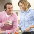 Mature couple preparing meal in domestic kitchen — Stock Photo #11888779