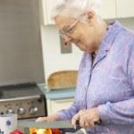 äldre kvinna hugga grönsaker i inhemska kök — Stockfoto #11888782