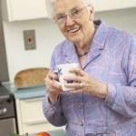 高级女人准备在国内厨房中的食物 — 图库照片