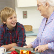 Grandmother and grandson preparing food in kitchen — Stock Photo