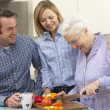 Senior woman and family preparing meal together — Stock Photo