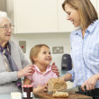 Multi-generation family preparing food in kitchen — Stock Photo