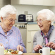 Senior women enjoying meal together at home — ストック写真