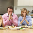 Family saying grace before meal — Stockfoto