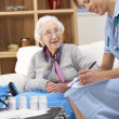 Royalty-Free Stock Photo: UK nurse visiting senior woman at home