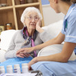 UK nurse visiting senior woman at home - Stock Photo