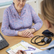 Senior woman patient with UK nurse — Stock Photo