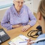 Senior woman patient with UK nurse — Stock Photo