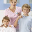 Mother and children cleaning teeth in bathroom — Stock Photo