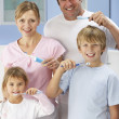 Family cleaning teeth together in bathroom — Stock Photo