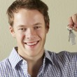 Studio Shot Of Young Man Holding Keys To First Home - Stock Photo