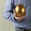 Stock Photo: Cropped Studio Shot Of MHolding Golden Egg