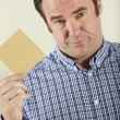 Studio Shot Of Middle Aged Man Holding Wage Packet - Stock Photo