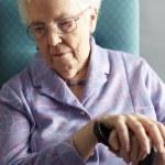 olycklig senior kvinna sitter i stol håller käpp — Stockfoto #11889243