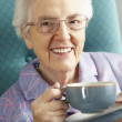 Senior Woman Relaxing In Chair With Hot Drink — Stock Photo #11889254