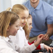 Stock Photo: Girls using computers in class with teacher