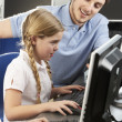 Stock Photo: Teacher helping girl using computer in class