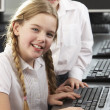 Girls using computers in school class - Stock Photo