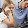 Royalty-Free Stock Photo: Unhappy teacher and girl using computer in class