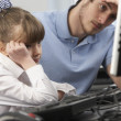 Unhappy teacher and girl using computer in class — Stock Photo