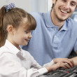 Teacher helping girl using computer in class - Stock Photo